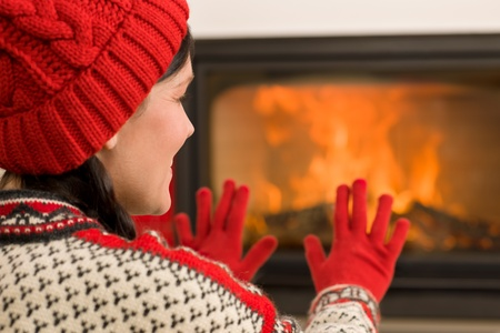 Happy woman warming up by home fireplace wear christmas sweater Stock Photo - 11288007