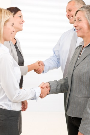 Business partners close successful deal happy people shaking hands agreement photo