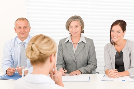 job satisfaction: Business interview young woman being examined by professional manager team
