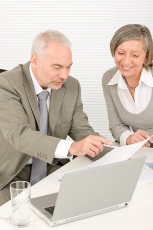Professional elegant happy senior businesswoman looking graphs with man colleague photo