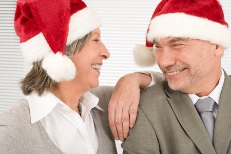 Laughing senior businesspeople having fun with Xmas Santa hat photo