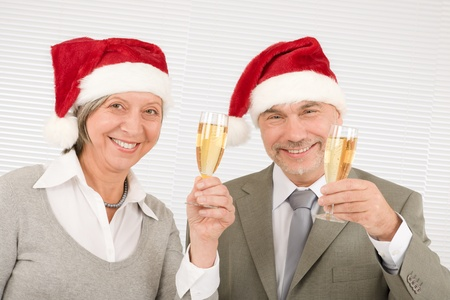 Laughing senior businesspeople wear Christmas Santa hat drink champagne photo