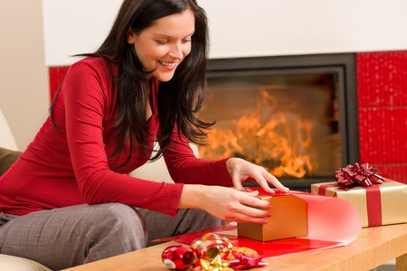Happy woman in red wrapping Christmas present by home fireplace Stock Photo - 11476097