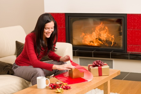 Happy woman in red wrapping Christmas present by home fireplace Stock Photo - 11476087