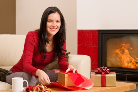 Happy woman in red wrapping Christmas present by home fireplace Stock Photo - 11476086