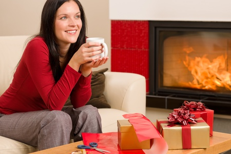 Happy woman wrapping Christmas present by fireplace enjoying hot drink photo