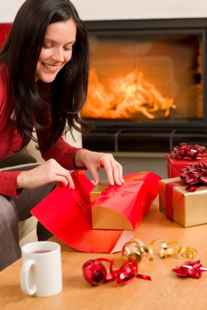 Happy woman in red wrapping Christmas present by home fireplace photo