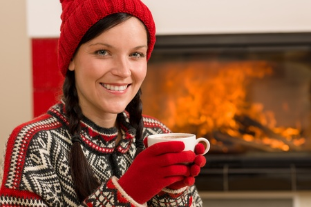 Winter christmas woman with hat and gloves drink by fireplace Stock Photo - 11476093