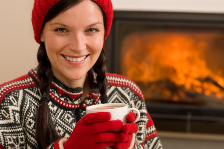 Winter christmas woman with hat and gloves drink by fireplace Stock Photo - 11476090