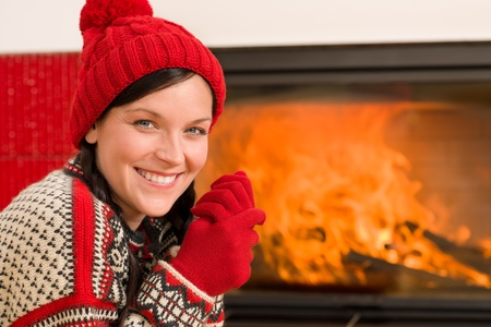 Happy woman warming up by home fireplace wear christmas sweater Stock Photo - 11476095