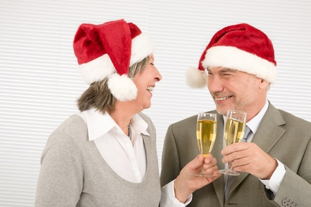 Laughing elegant senior businesspeople in Christmas hat drink champagne photo