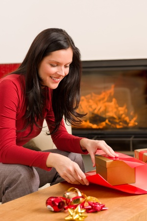 Happy woman in red wrapping Christmas present by home fireplace Stock Photo - 11476304