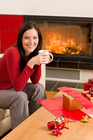 Happy woman wrapping Christmas present by fireplace enjoying hot drink Stock Photo - 11476315