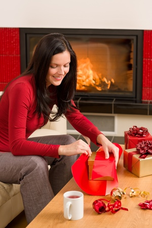 Happy woman in red wrapping Christmas present by home fireplace Stock Photo - 11476263