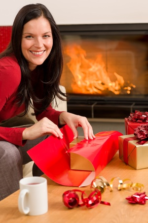 Happy woman in red wrapping Christmas present by home fireplace Stock Photo - 11476302