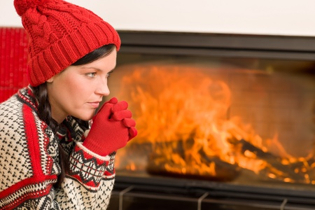 Happy woman warming up by home fireplace wear christmas sweater Stock Photo - 11464653