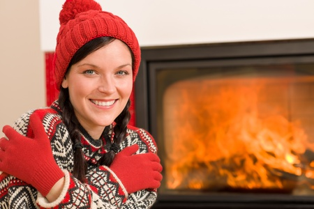 Happy woman warming up by home fireplace wear christmas sweater Stock Photo - 11476311