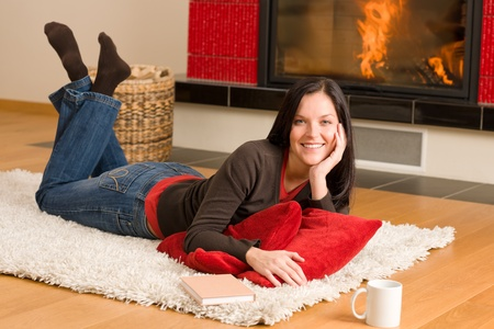 Happy young woman lying on rug by fireplace home living photo