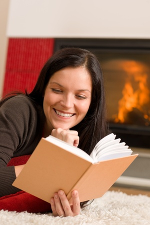 Happy young woman lying by fireplace on carpet reading book Stock Photo - 11476273