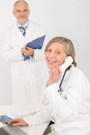 Medical senior doctor female calling with professional male colleague office photo
