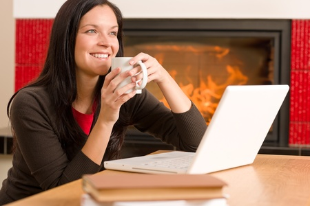 Happy woman at fireplace with laptop enjoying winter hot drink Stock Photo - 11476279
