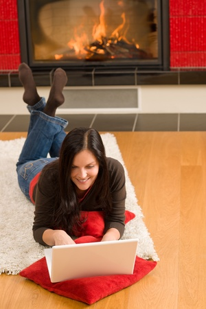 Home living happy young woman by fireplace working on laptop Stock Photo - 11476280