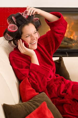 Home beauty woman with curlers calling phone fireplace red bathrobe Stock Photo - 11476416