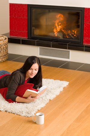 Happy young woman lying by fireplace on carpet reading book photo