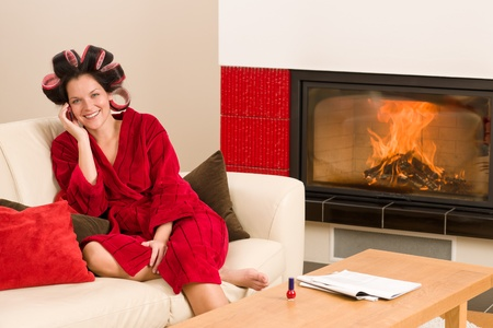 Home beauty woman with curlers calling phone fireplace red bathrobe Stock Photo - 11476261