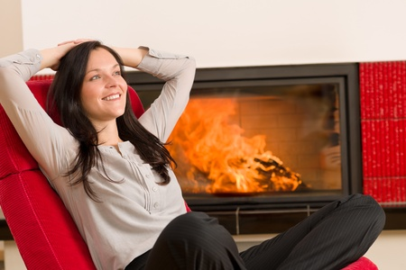 warm home: Young woman relax on red armchair by home fireplace