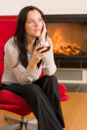 Young woman enjoying glass of red wine by home fireplace Stock Photo - 11476169