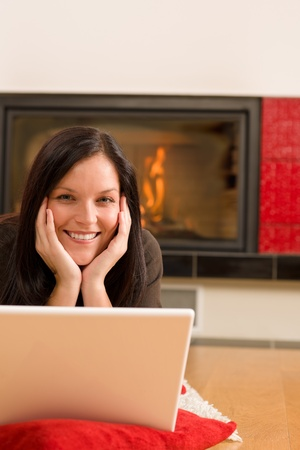 Home living happy young woman by fireplace working on laptop photo