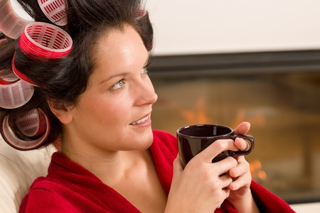 red bathrobe: Woman with curlers holding mug sitting by fireplace red bathrobe Stock Photo