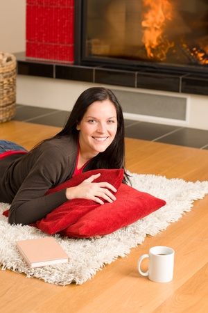 Happy young woman lying on rug by fireplace home living Stock Photo - 11476423