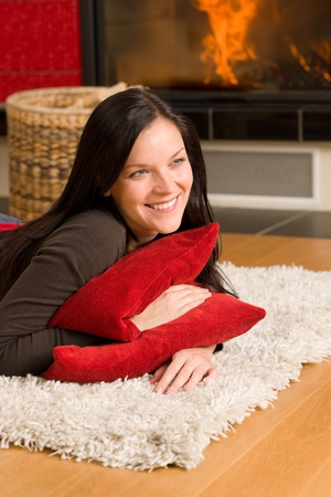 Happy young woman lying on rug by fireplace home living Stock Photo - 11476434