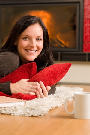 Happy young woman lying on rug by fireplace home living Stock Photo - 11476428