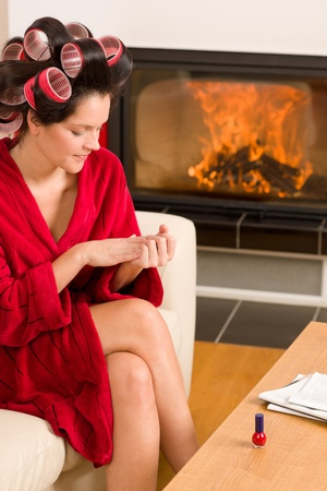 Home beauty woman with curlers checking manicure fireplace red bathrobe photo