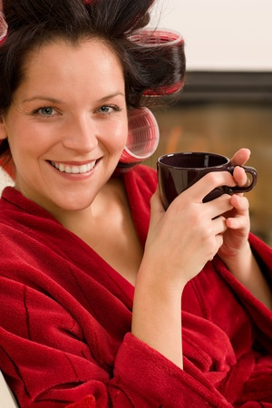 Woman with curlers holding mug sitting by fireplace red bathrobe Stock Photo - 11476456