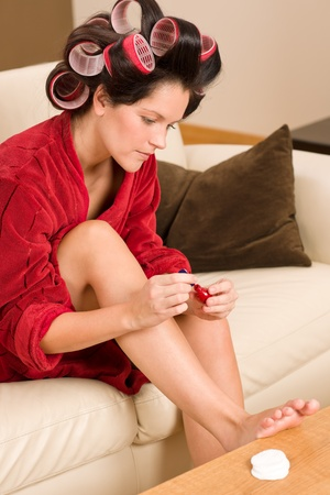 red bathrobe: Home beauty woman with curlers checking manicure nail polish fireplace