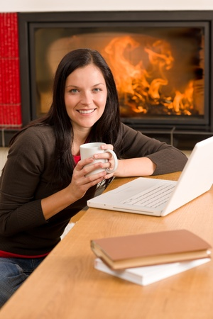 Happy woman at fireplace with laptop enjoying winter hot drink photo