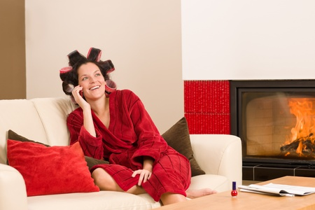Home beauty woman with curlers calling phone fireplace red bathrobe Stock Photo - 11476411