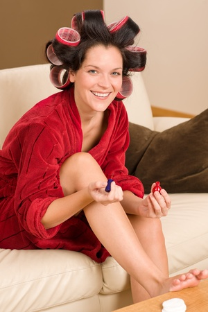 hair curler: Home beauty woman with curlers checking manicure nail polish fireplace