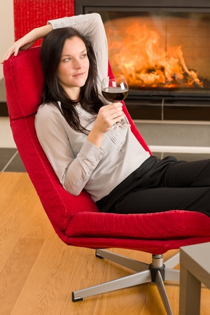 Young woman enjoying glass of red wine by home fireplace photo