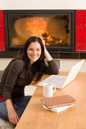 Happy woman at fireplace with laptop enjoying winter hot drink Stock Photo - 11476365