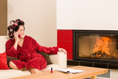 Home beauty woman with curlers calling phone fireplace red bathrobe photo