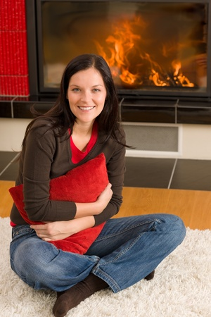 Beautiful happy young woman sitting front of home fireplace Stock Photo - 11476118