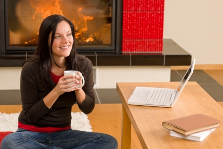 Happy woman at fireplace with laptop enjoying winter hot drink Stock Photo - 11476107