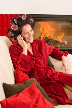 Home beauty woman with curlers calling phone fireplace red bathrobe