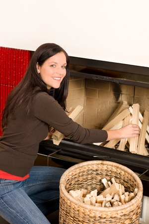 log basket: Young woman putting wood logs from wickerwork basket into fireplace