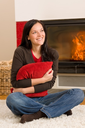 warm home: Beautiful happy young woman sitting front of home fireplace